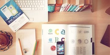 लैपटॉप, आईफोन और टेक्स्टबुक की विशेषता वाला डेस्कटॉप