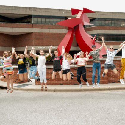 在行动拍摄的学生跳跃和手牵着手在雕塑前
