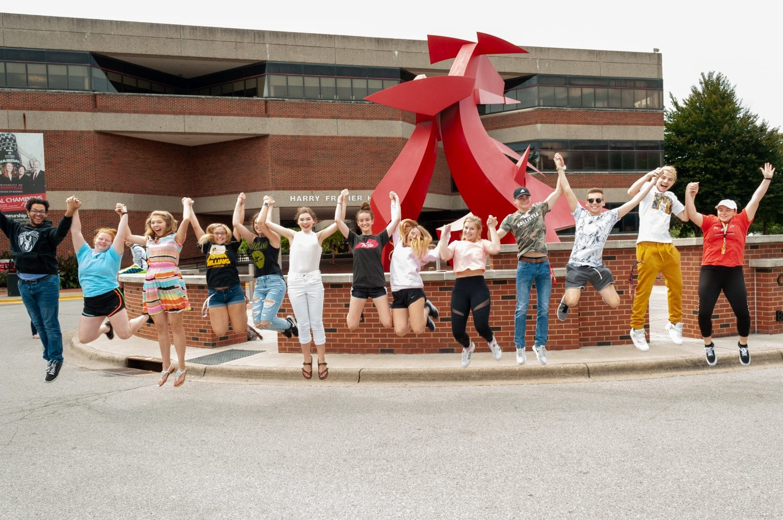 in action shot of students jumping and holding hands in front of sculpture