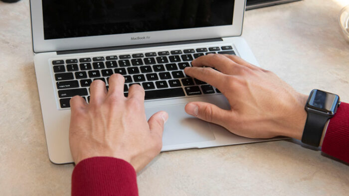 Closeup on hands typing on a MacBook air.
