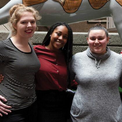 三个UofL女性新生商业专业互锁武器和站在Frazier Hall中庭。