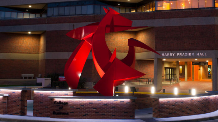The front of Frazier hall at night with sculpture in foreground.