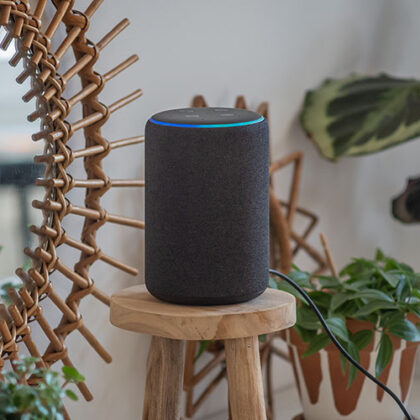 Amazon Alexa Echo Plus on a wooden table with green plants in the background
