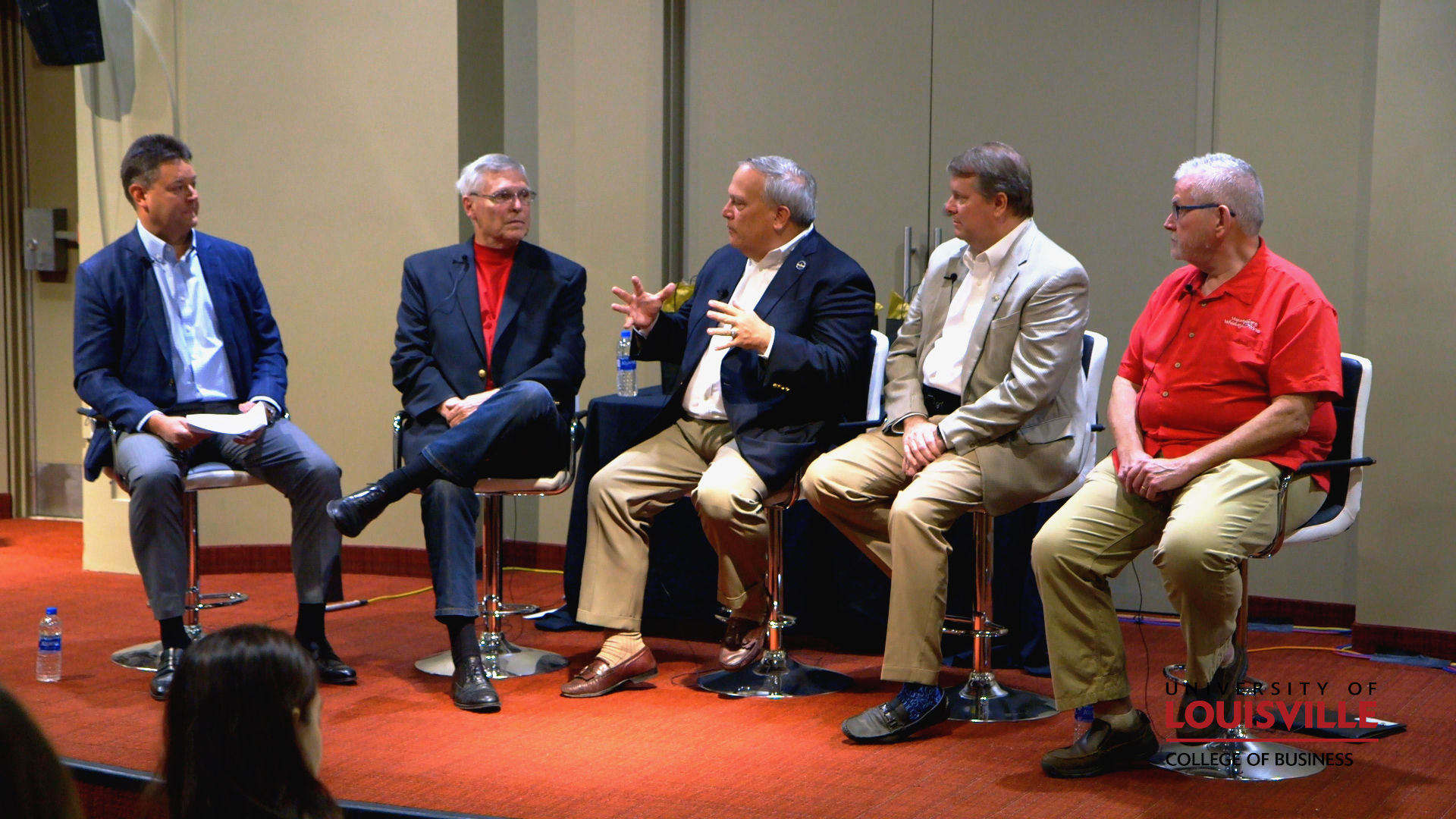 Five older businessmen discussing the state of the bourbon industry.