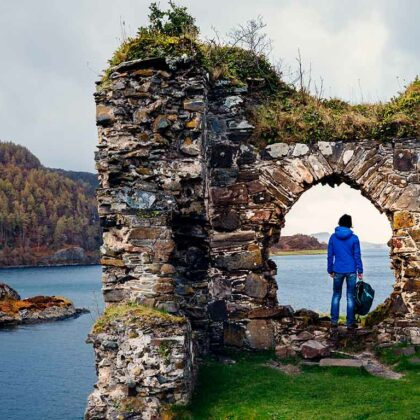 Female tourist at the ruins of Strome Castle on the shores of Loch Carron in the Wester Ross region of Scotland.