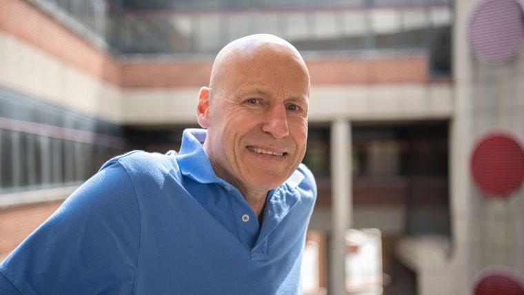 Стефан Гоман из Центра свободного предпринимательства при UofL стоит в атриуме Фрейзер-холла в солнечный день.