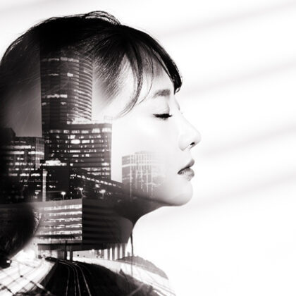 A double exposure of a young asian woman's side profile with the Atlanta skyline set within it.