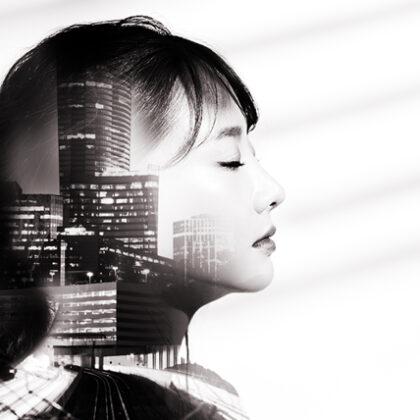 अटलांटा स्काईलाइन के साथ एक युवा एशियाई महिला की साइड प्रोफ़ाइल का दोहरा प्रदर्शन इसके भीतर सेट है।
