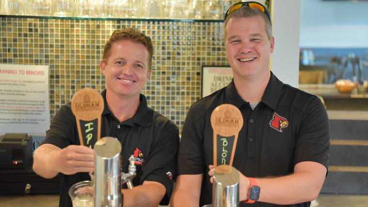 Brad Conrad and Steve Cayton from Oldham County Brewing opperating beer taps behind the bar.