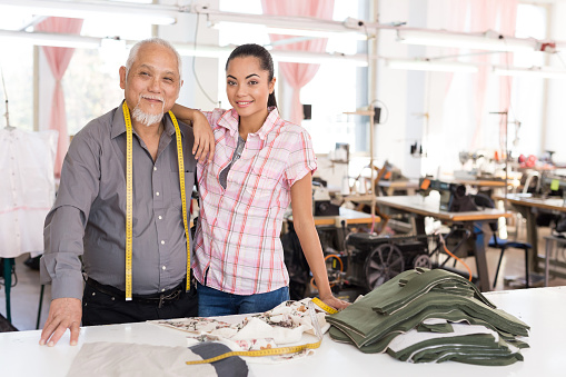 Father and daughter in textile factory, family business legacy in studio.